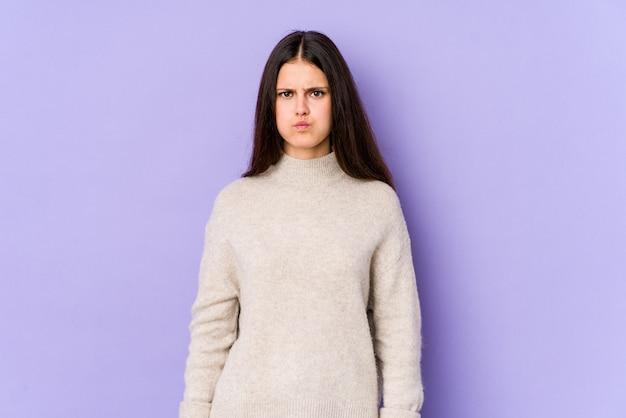 紫色の壁に若い白人女性は頬を吹く、疲れた表情をしています。