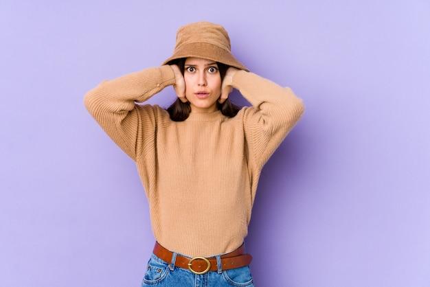 あまりにも大きな音が聞こえないようにしようと手で耳を覆う紫の壁に若い白人女性。