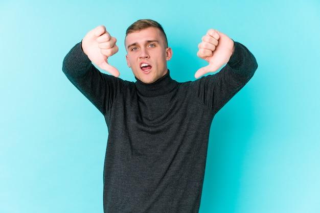 親指を示すと嫌悪感を表現する青い壁に若い白人男。