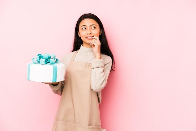 分離されたケーキを保持している若い中国人女性は、誇りと自信を持っていると感じています。