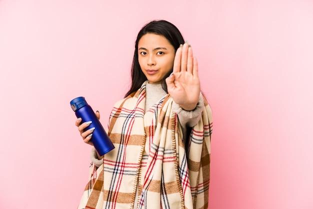 Молодая китайская женщина делая располагаться лагерем изолированный на розовой смущенной стене, чувствует сомнительным и неуверенным.