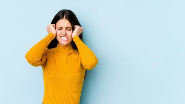 手で耳を覆う青い壁の若い白人女性。