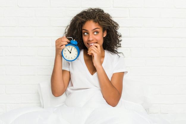 目覚まし時計を保持しているベッドに座っている若いアフリカ系アメリカ人女性は、コピースペースを見て何かについて考えてリラックスしました。