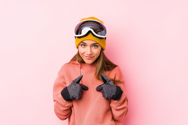 Молодая кавказская женщина нося одежду лыжи изолировала удивленный указывать с пальцем, широко усмехаясь.
