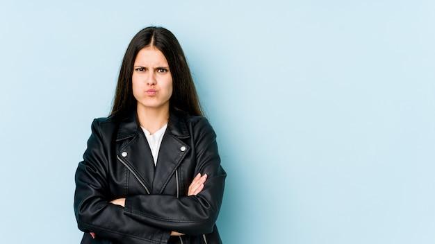青い壁に若い白人女性が頬を吹く、疲れた表情