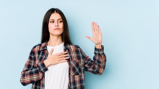 Молодая кавказская женщина на голубой стене принимая присягу, кладя руку на комод.