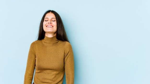 Молодая кавказская женщина на голубой стене смеется и закрывает глаза, чувствует себя расслабленной и счастливой.