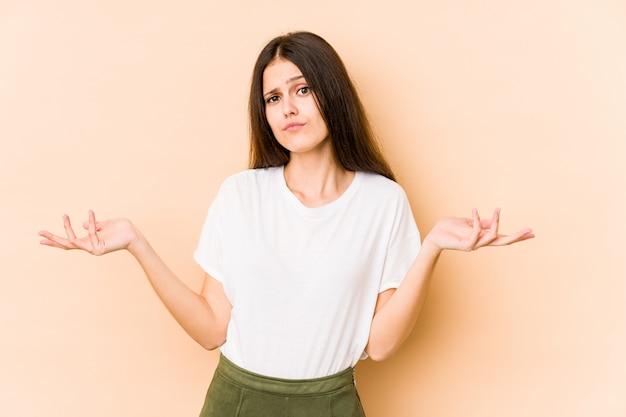 ジェスチャを疑って肩をすくめてベージュの壁に若い白人女性。