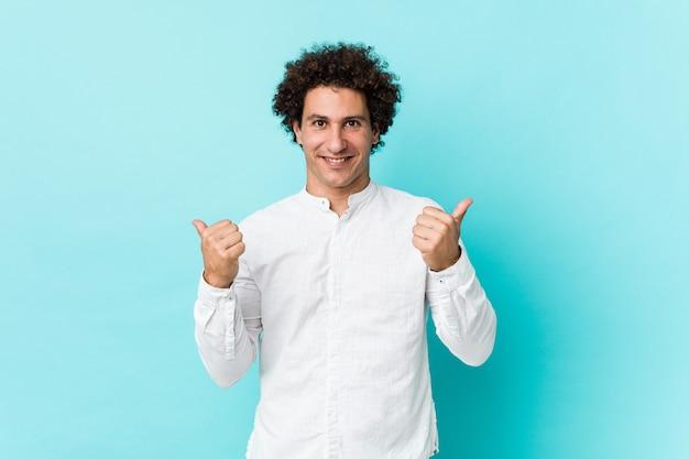 Молодой кудрявый зрелый человек в элегантной рубашке, поднимая оба больших пальца вверх, улыбаясь и уверенно.