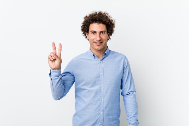 Молодой кудрявый зрелый человек в элегантной рубашке, показывая знак победы и широко улыбаясь.