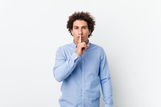 Молодой кудрявый зрелый человек в элегантной рубашке, сохраняя в тайне или прося молчания.