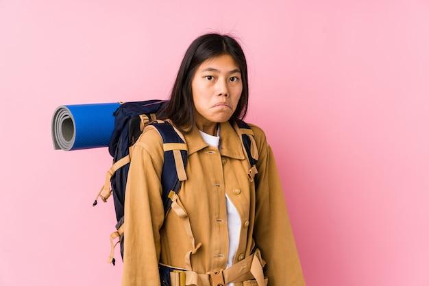 Молодая китайская женщина путешественника изолировала плечи пожиманий плечами и смущенные открытые глаза.