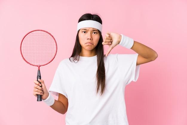 嫌いなジェスチャー、親指ダウンを示すピンクの壁でバドミントンを演奏若い中国人女性。不一致の概念。