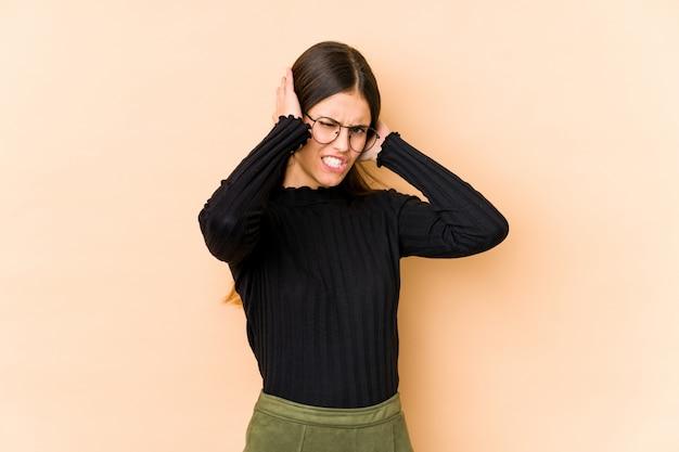 手で耳を覆うベージュの壁に若い白人女性。
