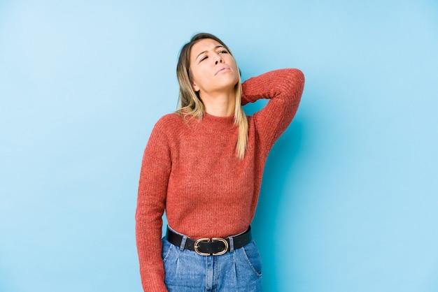 Молодая кавказская женщина представляя изолированную страдая боль в шее из-за сидячего образа жизни.
