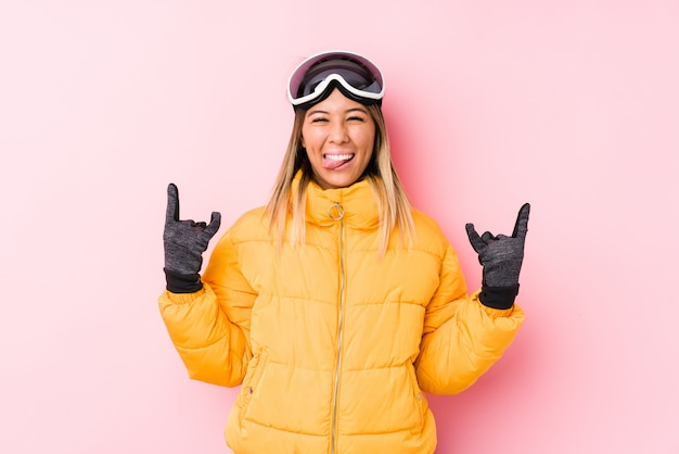 指でロックジェスチャーを示すピンクの壁でスキー服を着ている若い白人女性