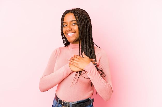 Молодая афроамериканка на розовом имеет дружелюбное выражение, прижимая ладонь к груди. концепция любви