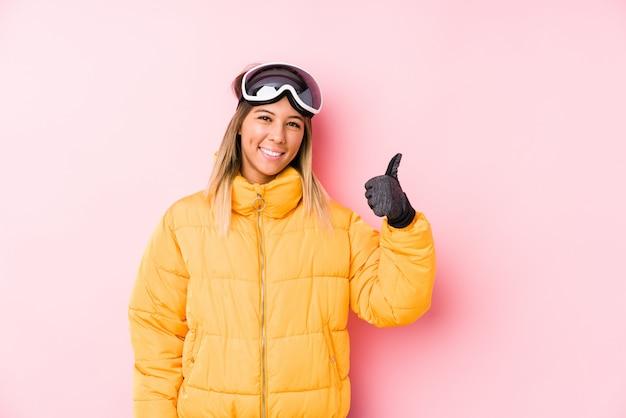 ピンクの笑顔と親指を上げるでスキー服を着た若い女性