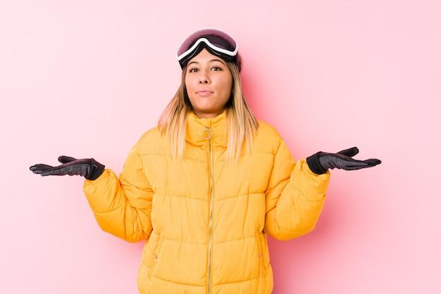 ピンクの疑わしいジェスチャーで肩をすくめてスキー服を着た若い女性。