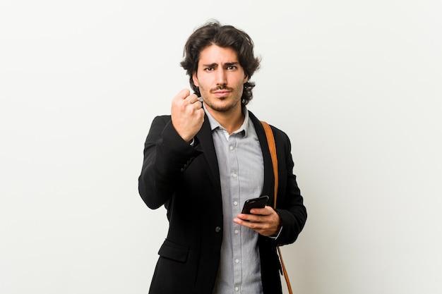 積極的な表情で拳を見せて電話を持って若いビジネスマン。
