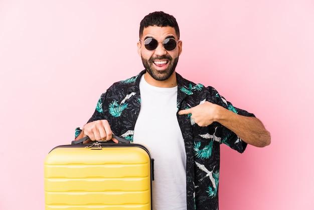 Молодой человек латинской держит чемодан удивленно указывая на себя, широко улыбаясь.