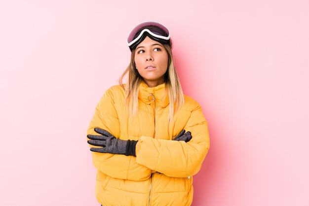 繰り返し作業にうんざりしているピンクのスキー服を着た若い女性。