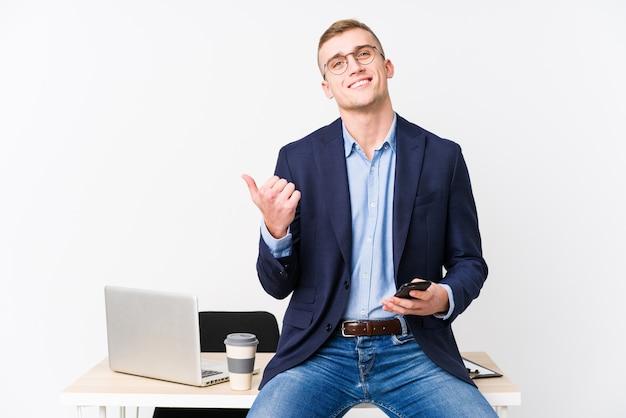 Молодой деловой человек с ноутбуком, улыбаясь и поднимая палец вверх