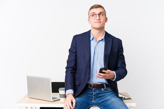 Молодой деловой человек с ноутбуком мечтает о достижении целей и задач