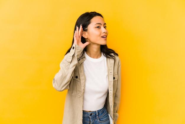 ゴシップを聴こうとしている黄色の壁に若い中国人女性。