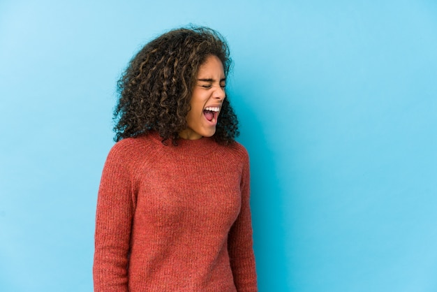 空白に向かって叫んでいる若いアフリカ系アメリカ人の巻き毛の女性