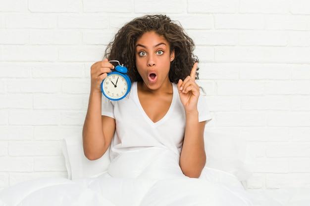 いくつかの素晴らしいアイデアを持つ目覚まし時計を保持しているベッドに座っている若いアフリカ系アメリカ人女性