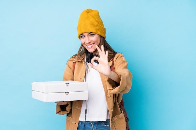 Молодая кавказская женщина держа пиццы жизнерадостные и уверенно показывая одобренный жест.