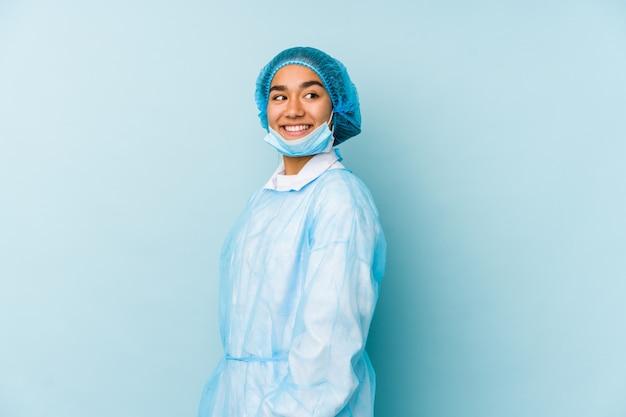 若い外科医のアジアの女性は笑みを浮かべて、陽気で快適な脇に見えます。