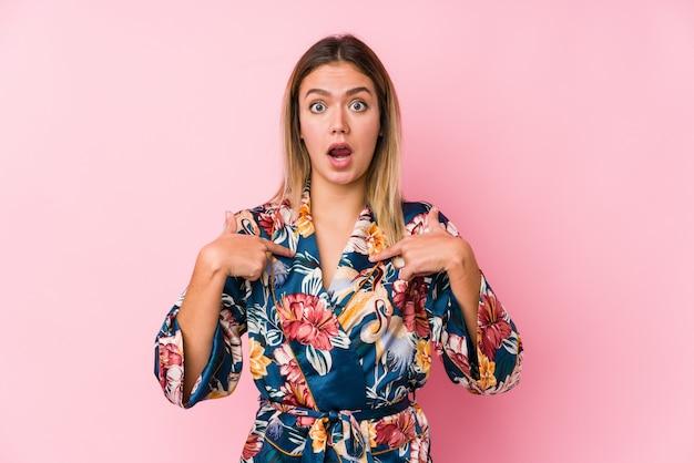 Молодая кавказская женщина в пижаме удивлен, указывая пальцем, широко улыбаясь.