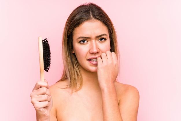 爪をかむ、神経質で非常に不安のヘアブラシを保持している若い白人女性。