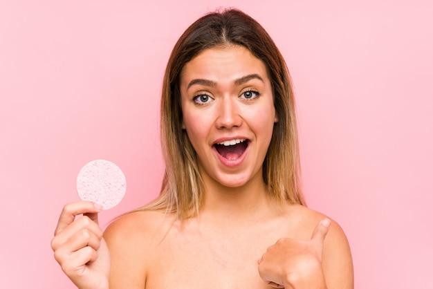 顔のディスクを保持している若い白人女性は、自分自身を指して驚いて、広く笑っています。