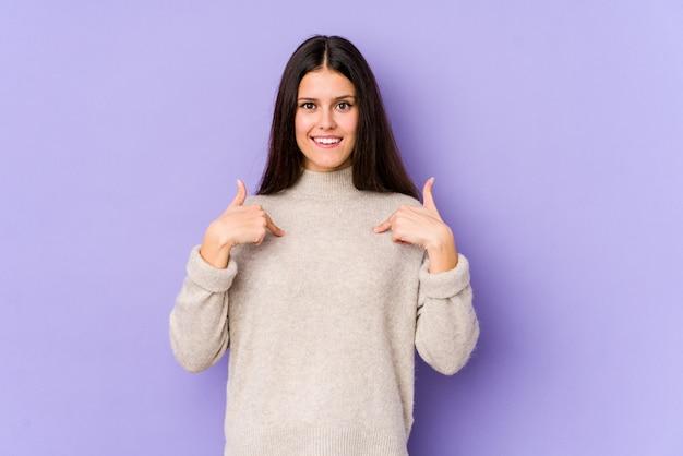 Молодая кавказская женщина на фиолетовой стене удивила указывать с пальцем, широко улыбаясь.