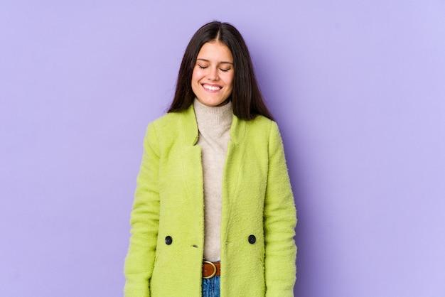 Молодая кавказская женщина на фиолетовой стене смеется и закрывает глаза, чувствует себя расслабленной и счастливой.