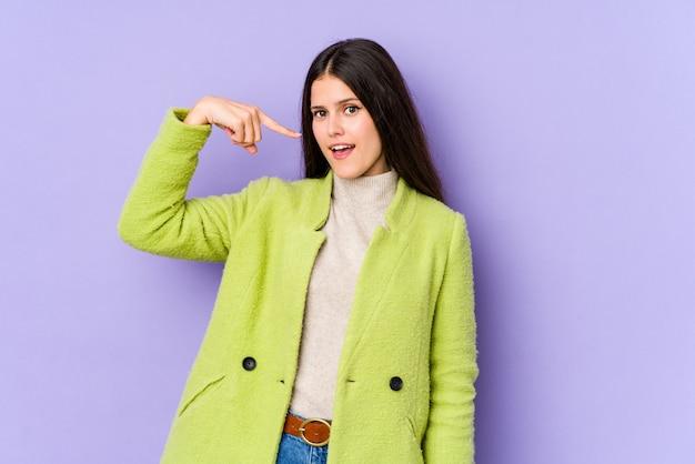 自分を指している紫色の壁人の若い白人女性