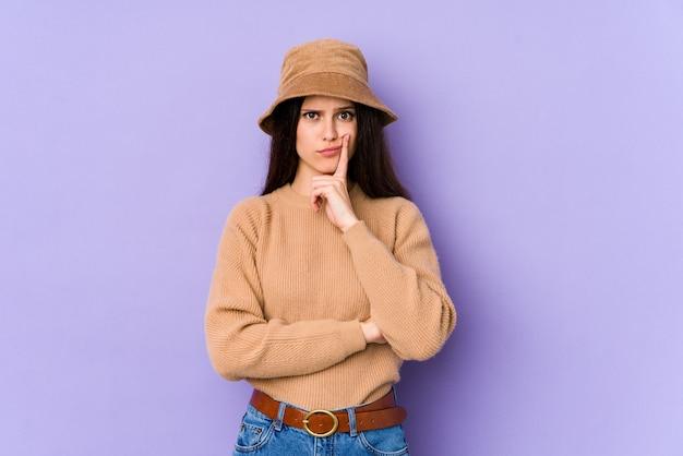 皮肉な表情で紫色の壁に若い白人女性。
