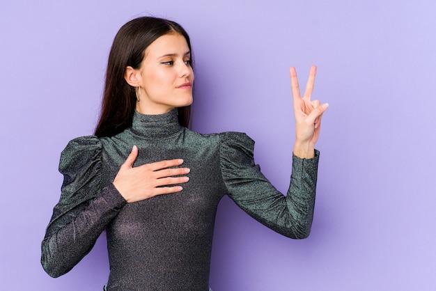 Молодая кавказская женщина на фиолетовой стене делая знак победы, кладя руку на комод.