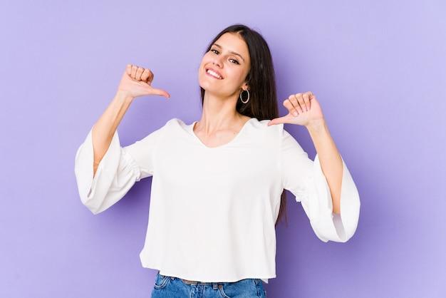 紫色の壁の若い白人女性は、誇りに思って、自信を持って、次の例です。