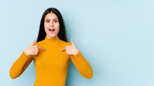 Кавказская девушка на голубой стене удивлен, указывая пальцем, широко улыбаясь.
