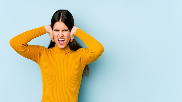 あまりにも大きな音が聞こえないようにしようと手で耳を覆う青い壁の若い白人女性。