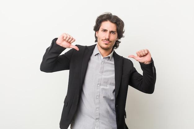 白い壁に立ち向かう若手実業家は、誇りと自信を持っていると感じています。