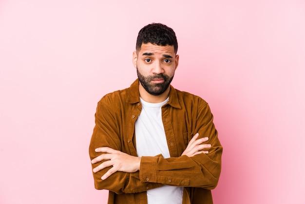 皮肉な表現に不満のピンクの壁に若いラテン男。