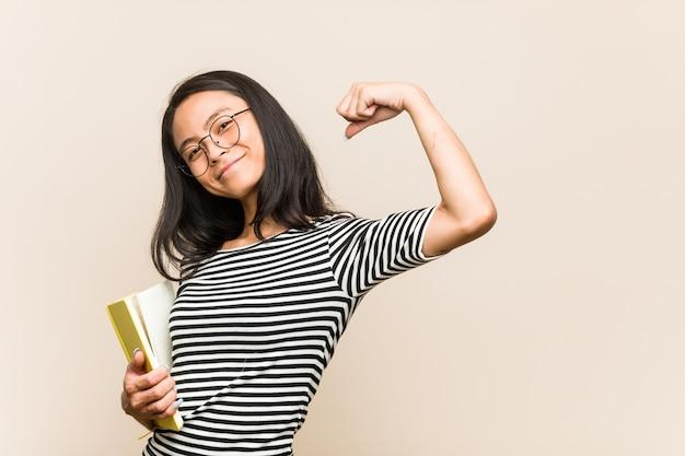 勝利後の拳を上げる本を持って若いアジア女性学生