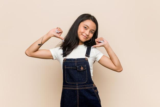 ピンクの壁に座っている若いかわいい中国のティーンエイジャーは、誇りと自信を持っていると感じています。
