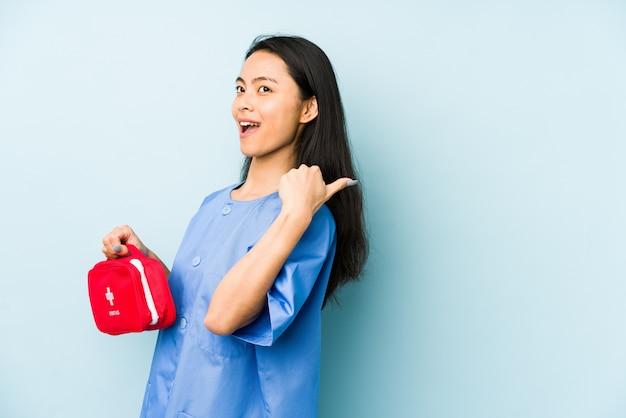 Молодая китайская медсестра на синей стене поднимает кулак после победы