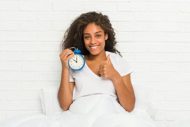笑みを浮かべて、親指を上げる目覚まし時計を保持しているベッドに座っている若いアフリカ系アメリカ人女性